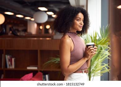 Young Businesswoman By Window With Takeaway Coffee Taking A Break In Modern Open Plan Office