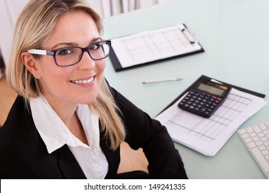 Young Businesswoman Calculating Data In Her Office