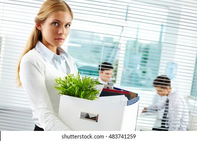 Young businesswoman with cardboard box being fired