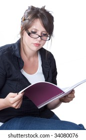 A young businesswoman in casual attire reviews her planner; isolated on a white background.