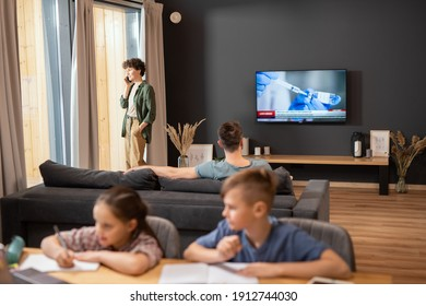 Young businesswoman in casualwear talking on mobile phone by large window while her husband watching news about vaccination on tv