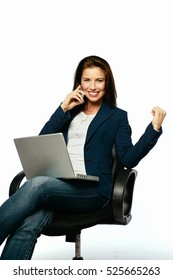 Young Businesswoman celebrating in an office chair while talking on her phone and with laptop on her lap.