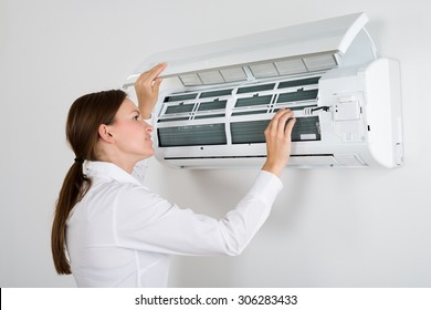 Young Businesswoman Checking Air Conditioner Mounted On Wall In Office