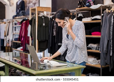 Young businesswoman checking laptop in her clothing store. Young entrepreneur using laptop and talking on mobile. Store manager woman checking important documents on laptop. Small business concept.