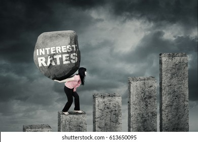 Young businesswoman climbing a diagram while carrying a big stone with text of interest rates