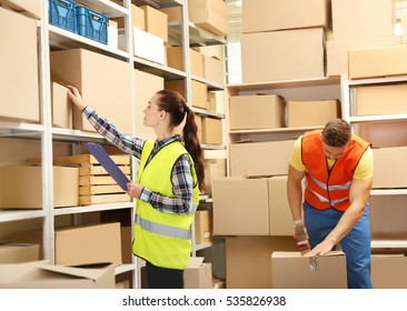 Young businesswoman with clipboard at warehouse