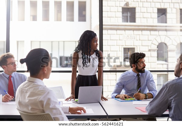 Young businesswoman and colleagues at meeting, looking away