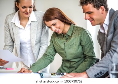 Young businesswoman with colleagues working at desk in office