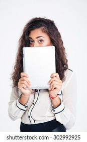 Young businesswoman covering her face with tablet computer and looking at camera isolated on a white background