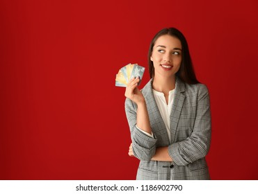 Young businesswoman with credit cards on color background