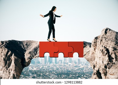 Young businesswoman crossing abstract jigsaw bridge on sky background. Teamwork and balance concept