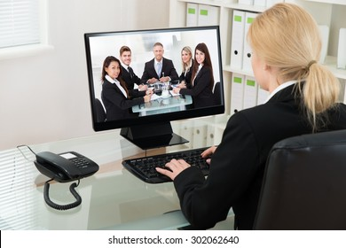 Young Businesswoman At Desk Video Conferencing With Colleagues On Computer In Office