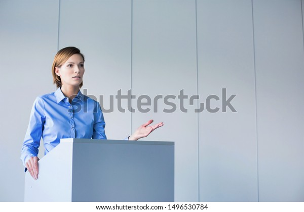 Young businesswoman discussing business plan to colleagues in conference room