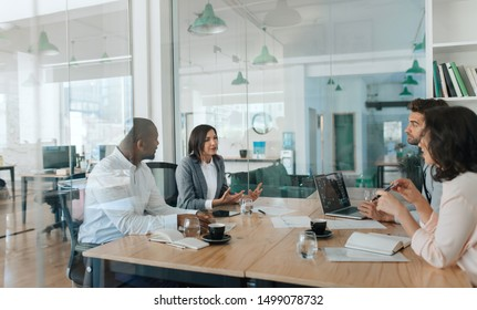 Young businesswoman discussing work with a diverse group of colleagues during a meeting together inside of a glass office