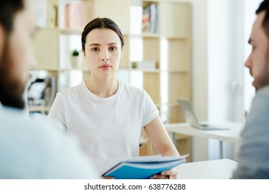 Young businesswoman with documents looking at camera by workplace