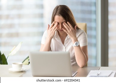 Young businesswoman doing exercises at workplace to relieve tired of computer eyes, massaging closed eyelids to relax muscles, reduce tension, improve vision, yoga for eye strain, eyesight relaxation