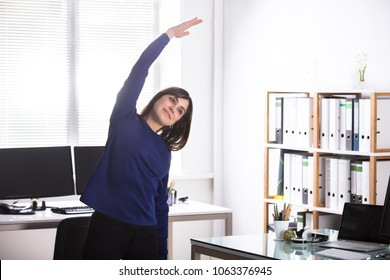 Young Businesswoman Doing Stretching Exercise In Office