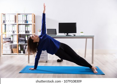 Young Businesswoman Doing Stretching Exercise On Exercise Mat At Workplace