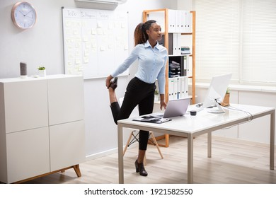 Young Businesswoman Doing Yoga Standing In Front Of Office Desk