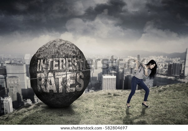 Young businesswoman dragging a boulder with success word while walking on the hill