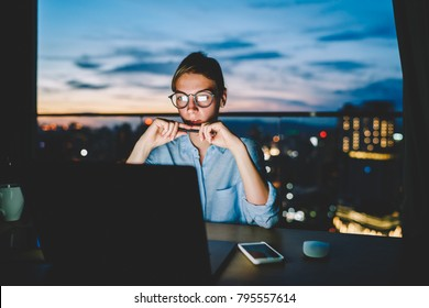 Young businesswoman dressed in shirt reading useful article about creative ideas for startup project on laptop computer.Pensive female person working overtime late at night office using modern gadget