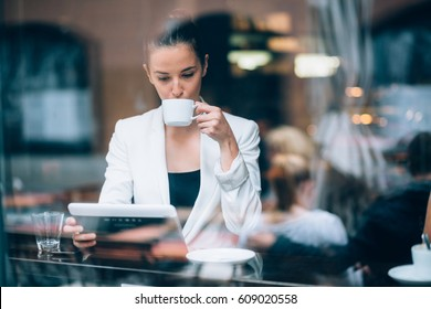 Young businesswoman drinking coffee and using tablet computer in cafe