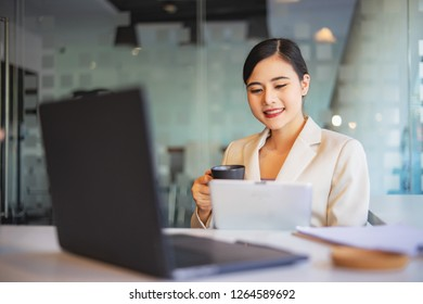 Young businesswoman drinking while sitting at her desk in an office reading report