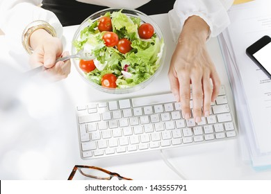 Young businesswoman eating a salad while working in office. /Young businesswoman typing on the laptop.