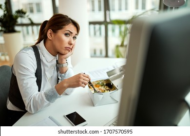Young businesswoman eating and thinking of something in the office.