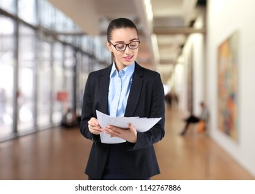 Young businesswoman in elegant suit with documents on blurred background