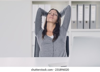 Young businesswoman enjoying a relaxing moment sitting in her chair at her desk with her hands clasped behind her head and eyes closed with a serene expression