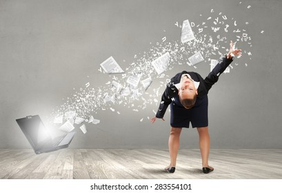 Young businesswoman evading papers flying from laptop