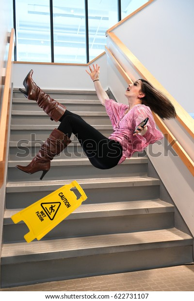 Young businesswoman falling on stairs inside office building