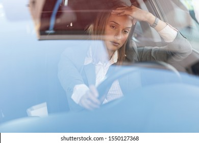 Young businesswoman feeling annoyed while driving a car and being stuck in a traffic jam. The view is through the glass.