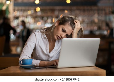 Young businesswoman feeling depressed while using computer in cafeteria