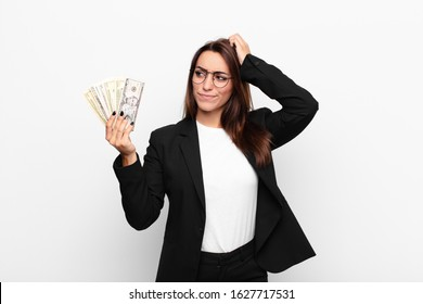 young businesswoman feeling puzzled and confused, scratching head and looking to the side with dollar banknotes