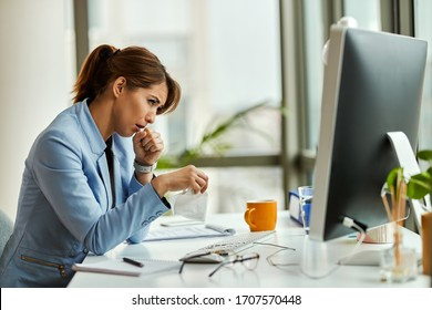 Young businesswoman feeling sick and coughing while working on a computer in the office.