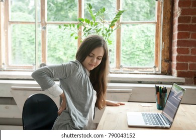 Young businesswoman feels uncomfortable sitting in office chair, woman massaging her back suffering from discomfort ache pain, incorrect posture from long sedentary work and lower backache concept