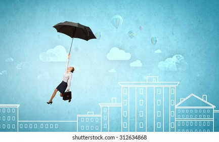Young businesswoman flying high in sky on black umbrella