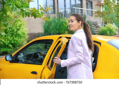 Young businesswoman getting into taxi car