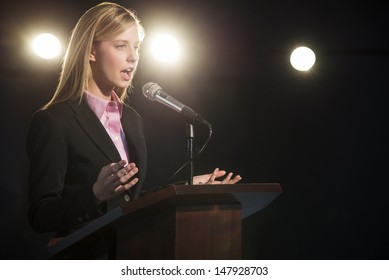 Young businesswoman giving speech at podium in auditorium