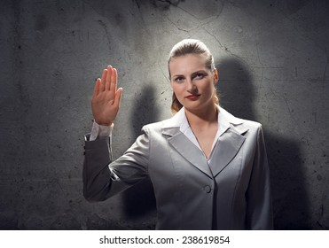 Young businesswoman with hand up taking an oath
