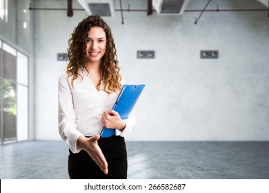 young businesswoman with handshake gesture in a rendered empty industrial room