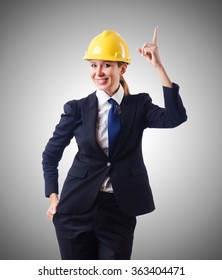 Young businesswoman with hard hat against gradient
