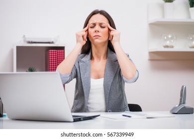 Young businesswoman is having headache at work.