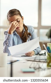 Young businesswoman with headache working on paperwork and analyzing financial reports in the office.