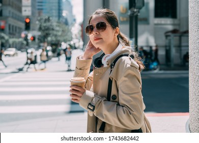 Young businesswoman with headphones and to go coffee on street. elegant office lady waiting to cross zebra road in busy urban. female worker with earphones and hands holding paper cup of hot beverage