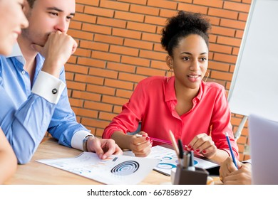 Young businesswoman with her colleagues listening to presentation in the meeting