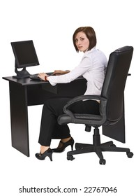 Young businesswoman at her desk working on the computer and looking back over the shoulder.