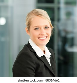 Young businesswoman in her office; she is looking into the camera